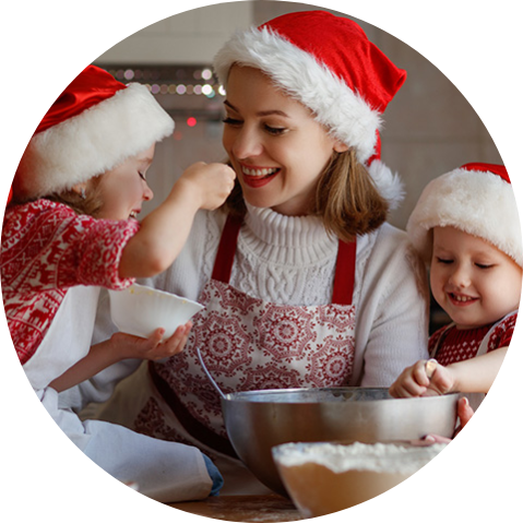 woman wiht kids baking and wearing santa hats