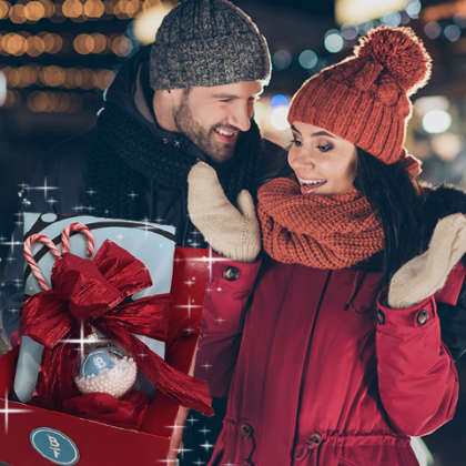 man and woman in winter clothes with gift basket